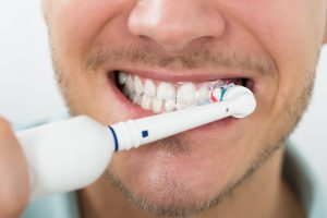 man brushing teeth with electric toothbrush