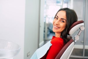 a woman sitting and smiling in the dentist's chair