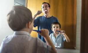Father and son brushing while away from dentist in Henderson.