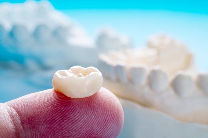 an up-close view of a dental crown resting on the tip of a person's finger