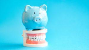 Blue piggy bank on top of model dentures